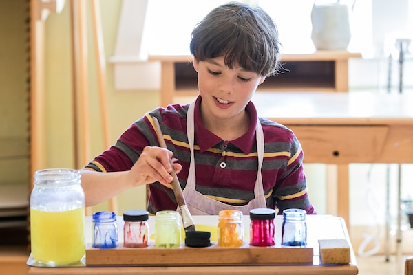 Boy doing water color painting with brush and jars of paint.