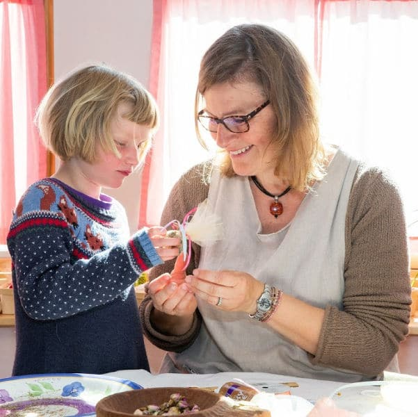 Early Childhood teacher helps student with handwork project.