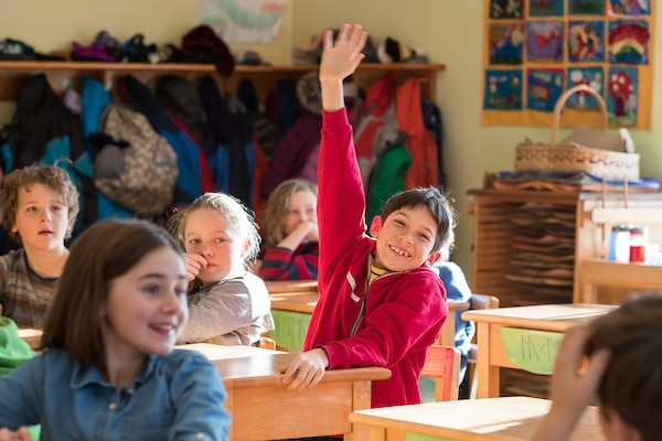 Grade school student raises hand in classroom as other students look on.